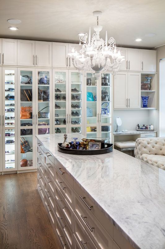 Walk-in Closet with shoes and purses behind glass mullion doors and Walk-in Closet with shoes and purses behind glass mullion doors