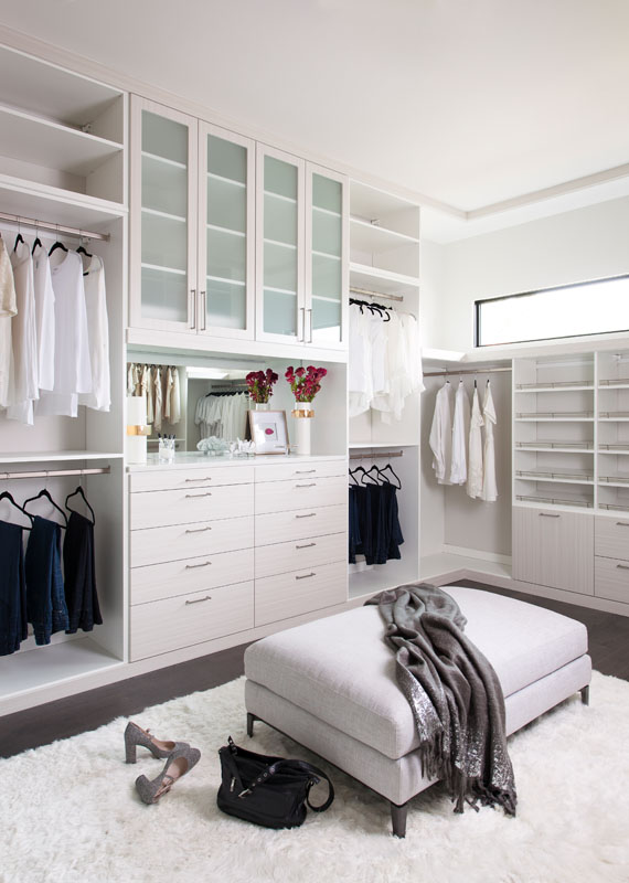 Custom closet to the ceiling with an ottoman or island allows space to live in today's custom closets
